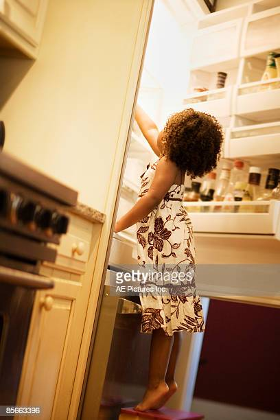 Girl reaches in refrigerator