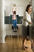 Girl reaching for cookie jar in kitchen with mother