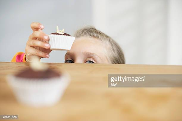 Girl (5-7) reaching for cupcake off counter, high section
