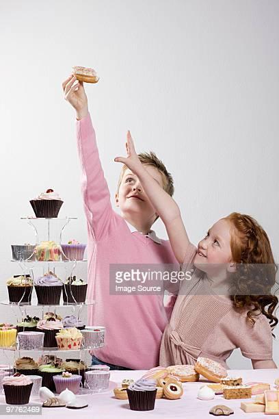 Girl reaching for doughnut that boy is holding