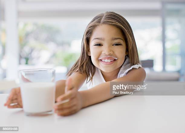 Girl reaching for glass of milk