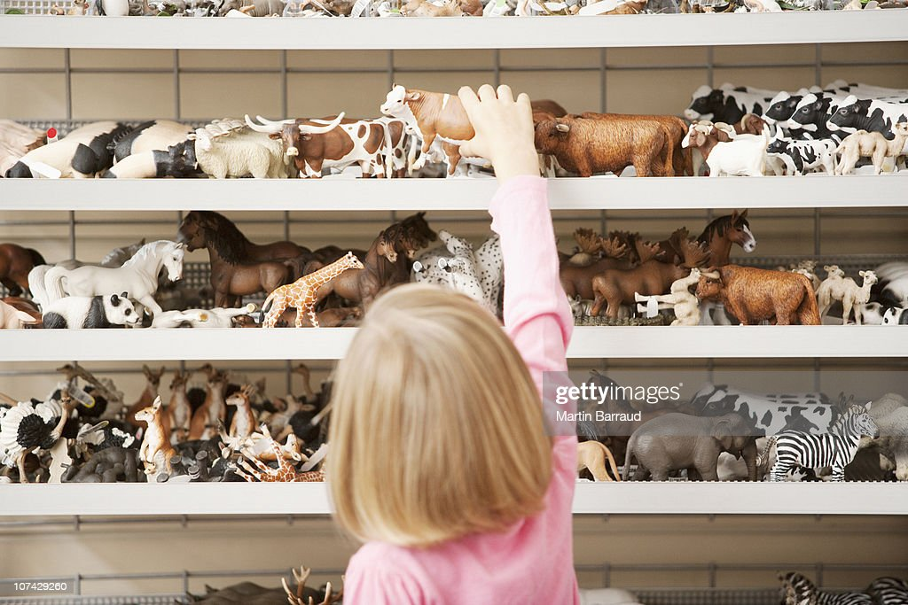Girl reaching for plastic cow in toy store : Stock Photo