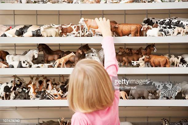 Ragazza raggiungendo per giocattolo di plastica nel negozio di mucca