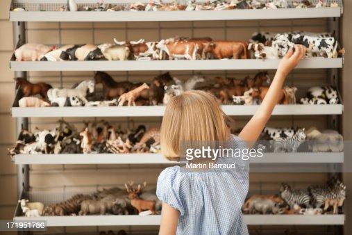 Menina alcançar para vacas de plástico em Loja de Brinquedos