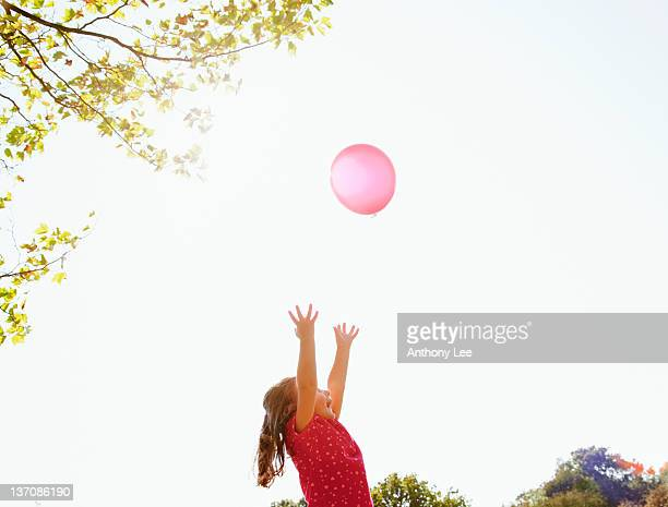 Girl reaching for red balloon in sunny sky