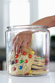Girl (4-6) reaching into cookie jar, close-up