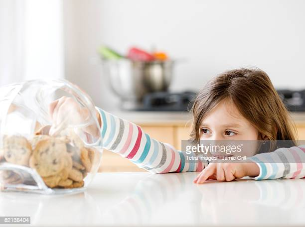 Girl reaching into cookie jar