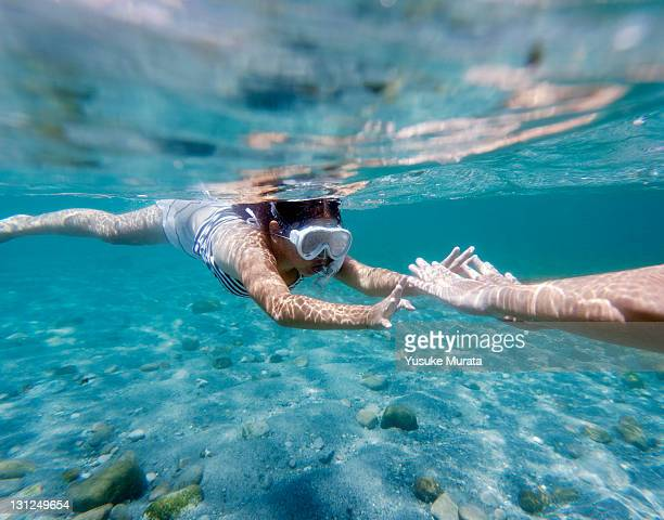 girl reaching to father's hands in the sea.