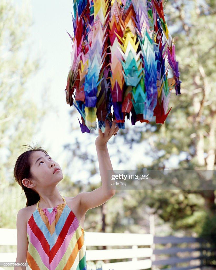 Girl Reaching Up Touching Origami Paper Cranes Above Head Foto de ...