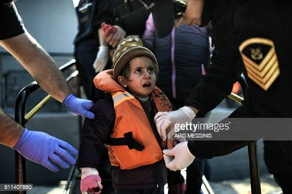 TOPSHOT A girl reacts as members of the Greek coast guard remove her life jacket as migrants and refugees arrive at the port of the northern island...