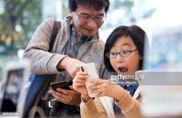 A girl reacts as she tries an iPhone X at the Apple Omotesando store on November 3 2017 in Tokyo Japan Apple launched the latest iPhone featuring...