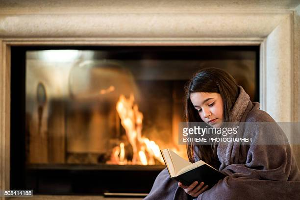 Girl reading a book by the fireplace