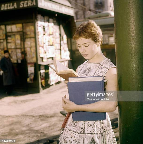 A girl reading a book in the street in front of a newspaper kiosk Italy 1960s