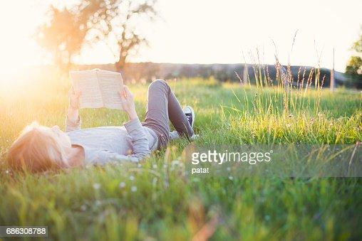 Girl reading a book outside header : Stock Photo