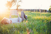 Young girl reading a book in the grass while sun setting down. Summer feeling.