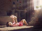 Cute little child girl reading a book.