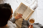 beautiful brunette girl reading book and drinking coffee in bed in the morning