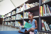 Girl reading book while sitting by shelf in library