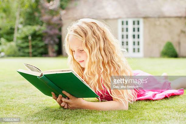 Girl reading book in backyard