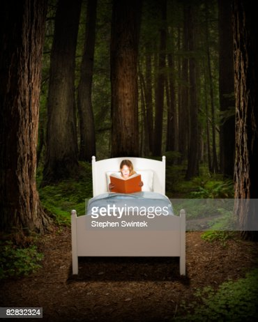 Girl reading book in bed located in a forest