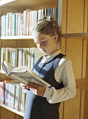 Girl (5-7) reading book in library