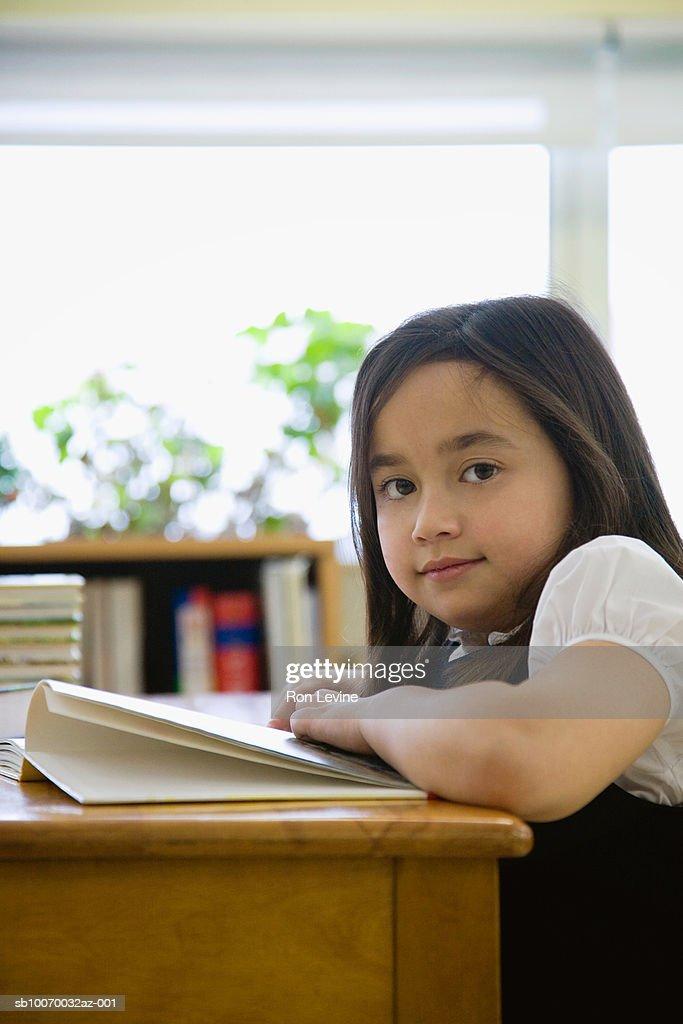Girl (6-7) reading book in school library, portrait