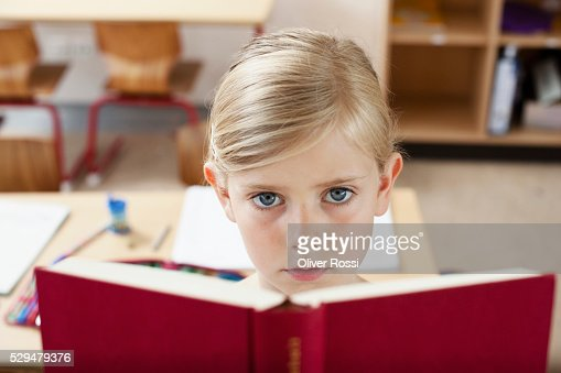 Girl reading book in school : Stock-Foto