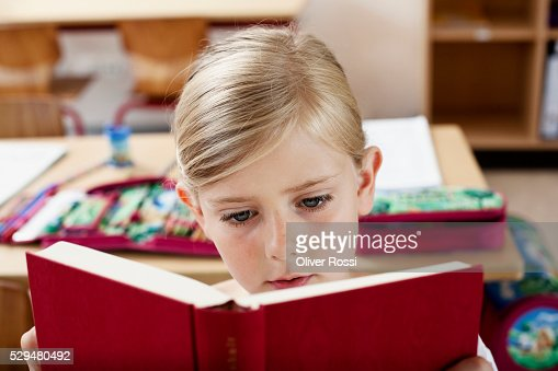 Girl reading book in school : Stockfoto