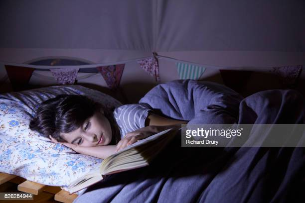 Girl reading book in tent at night