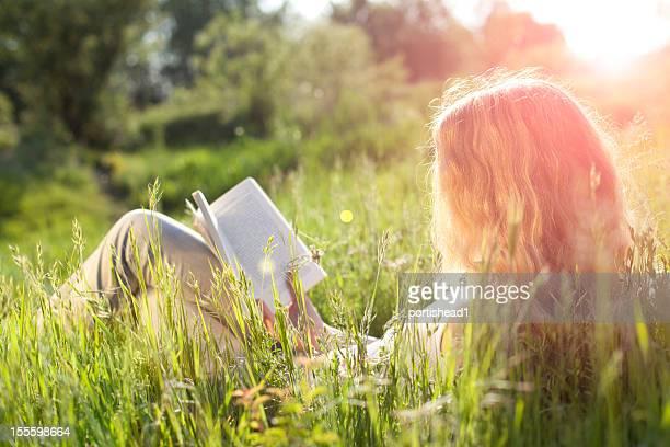 Niña leyendo libro en el campo