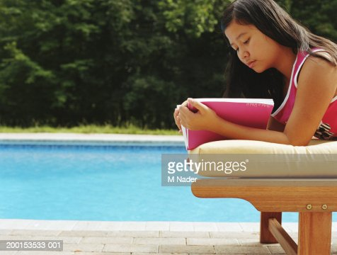 girl reading book near swimming pool side view stock photo getty images