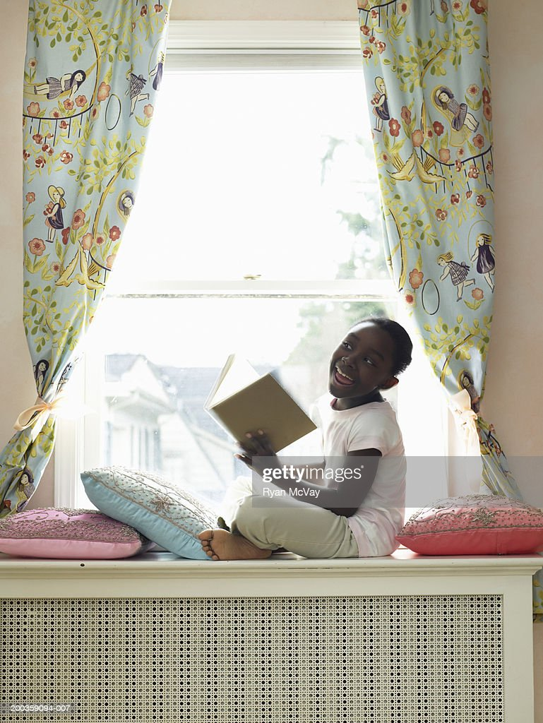 Girl (7-9) reading book on window seat, smiling, side view