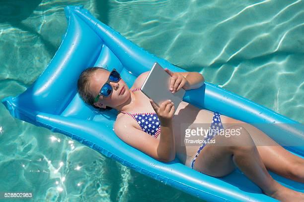 Girl reading digital book in swimming pool