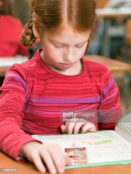 Girl (4-7) reading exercise book, close-up
