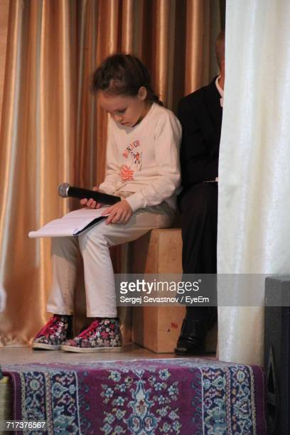 Girl Reading From Paper While Sitting On Box Against Wall On Stage