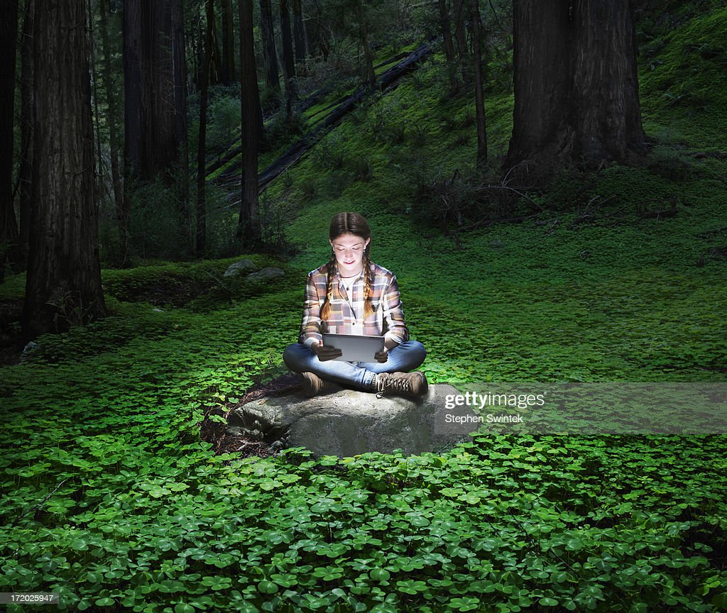 Girl reading glowing tablet in redwood forest : Stock Photo