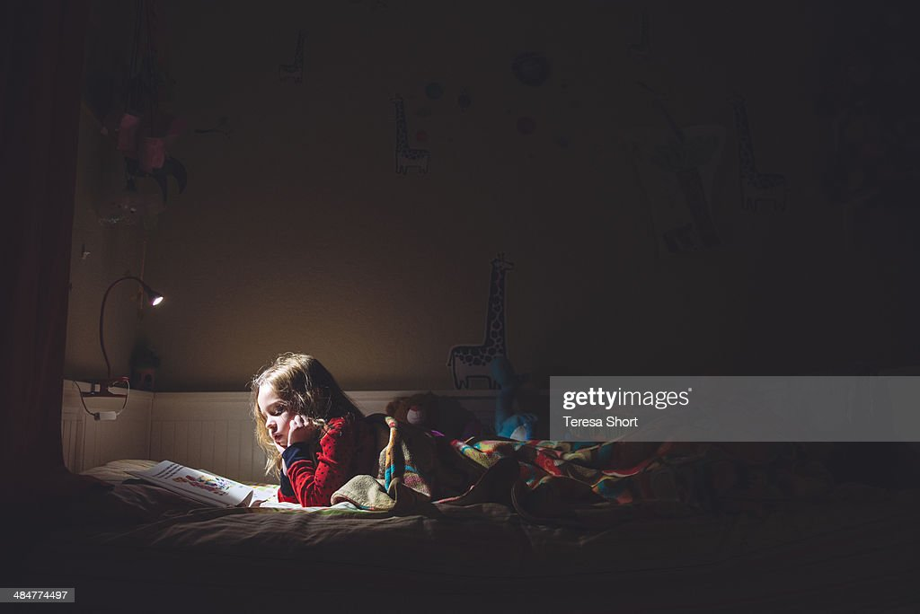 Girl reading in her bed at night : Stock Photo