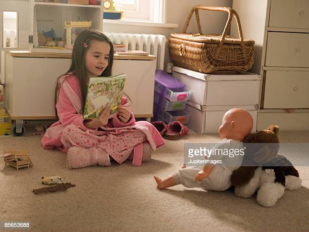 Girl reading to doll
