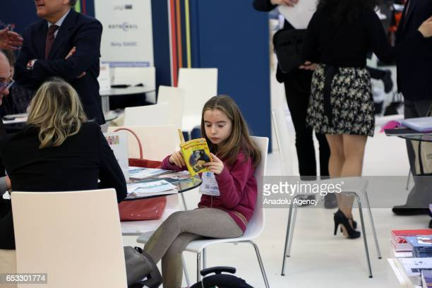 A girl reads a book at the Olympia Fair Center during the 46th London Book Fair the global marketplace for rights negotiation and the sale and...