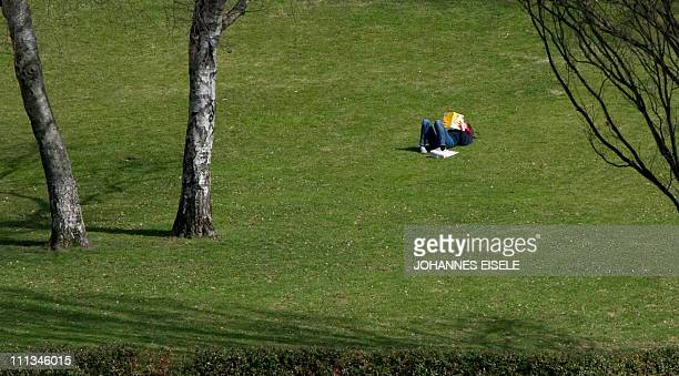 A girl reads a book in a park on April 1 2011 in Berlin Spring has arrived in the German capital with temperatures predicted to reach up to 23...