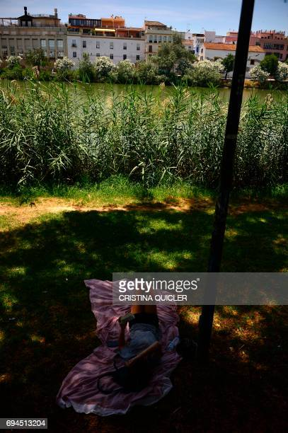 A girl reads a book in the shade beside the Guadalquivir river in Sevilla on June 10 2017 QUICLER