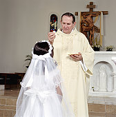 Girl (5-7) receiving communion bread at first holy communion