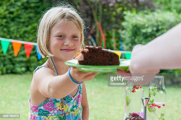 Girl receiving piece of cake on a birthday party