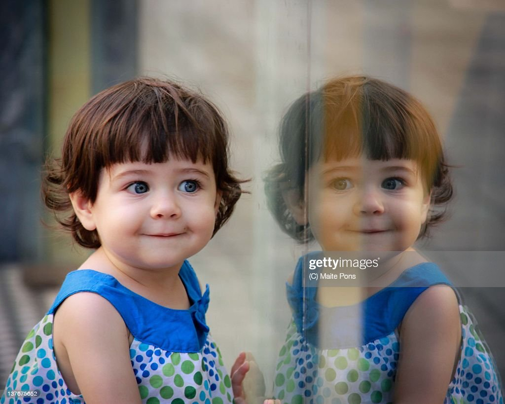 Girl reflected in shop window : Stock Photo