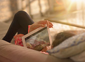 A girl relaxing at home watching a film on an iPad