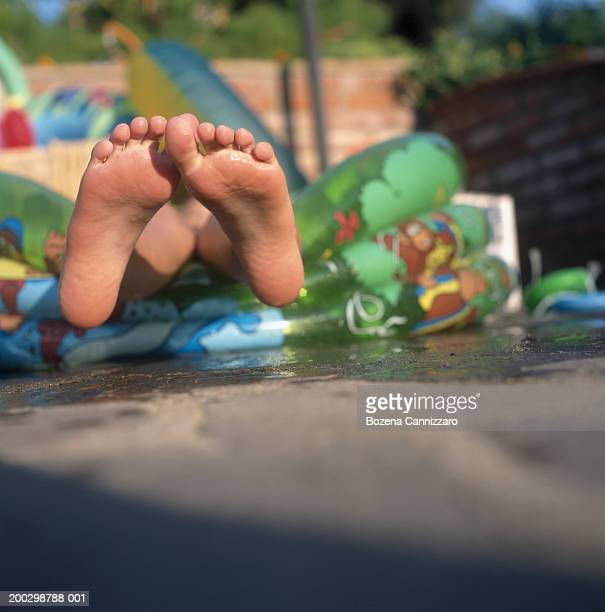 Girl (5-7) relaxing in paddling pool, feet over side, low section