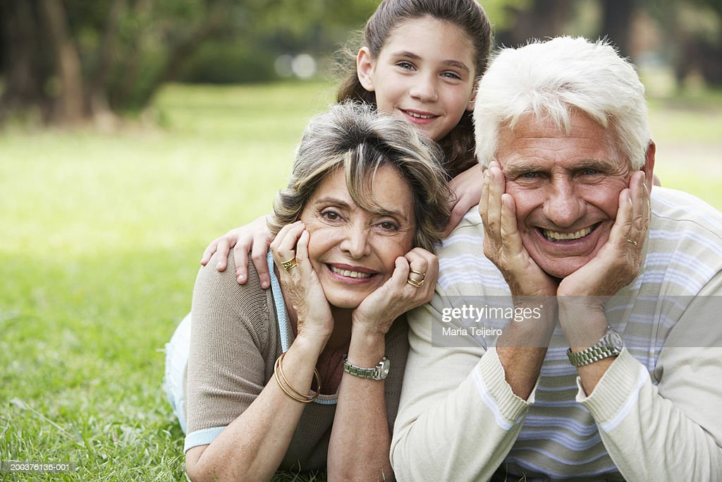 Girl (8-10) relaxing in park with grandparents, smiling, portrait