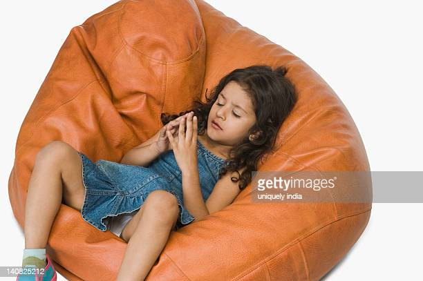 Girl relaxing on a bean bag and wishing
