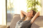 Portrait of a girl relaxing on a sofa after work at home sitting on a sofa in the living room at home with a warm light of sunset