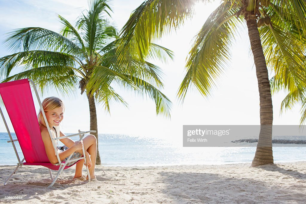 Girl (10-11) relaxing on beach lounger : Stock Photo
